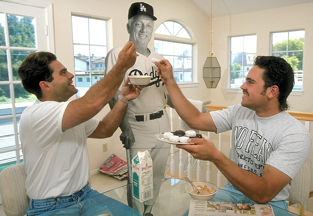 Los Angeles Dodgers teammates and roommates Eric Karros and Mike Piazza feed cereal and doughnuts to a cut-out of their manager, Tommy Lasorda, on June 5, 1993 in Los Angeles.