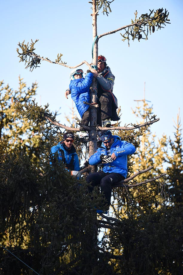 Coaches and children watch the FIS Alpine World Cup men's downhill from a tree in Northern Italy.