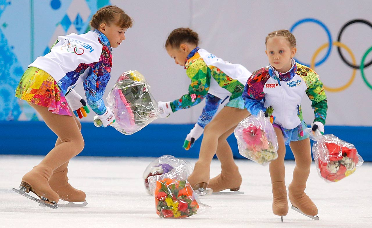 Flower girls pick up bouquets thrown on to the ice by spectators following the routine by Ekaterina Bobrova and Dmitri Soloviev of Russia.