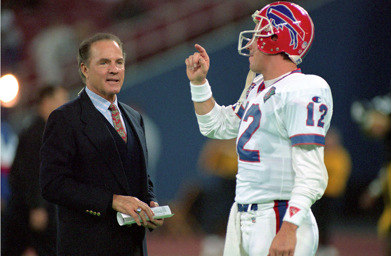 Frank Gifford talks with quarterback Jim Kelly of the Buffalo Bills before a game against the Pittsburgh Steelers at Three Rivers Stadium in  November 1994.