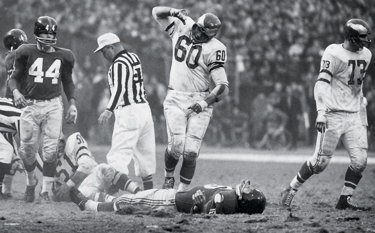 Frank Gifford lays motionless while Philadelphia Eagles linebacker Chuck Bednarik celebrates a hit that put the New York Giant out of a November 1960 game.