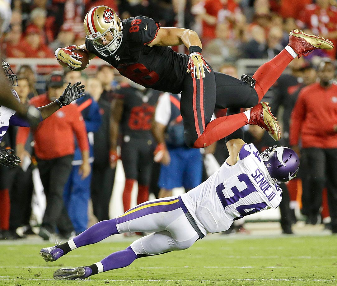 San Francisco tight end Garrett Celek is tackled by Minnesota strong safety Andrew Sendejo.