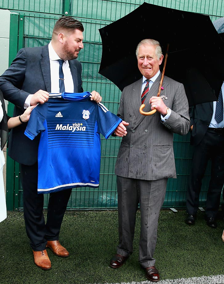 Prince Charles is presented with a Cardiff City football shirt.