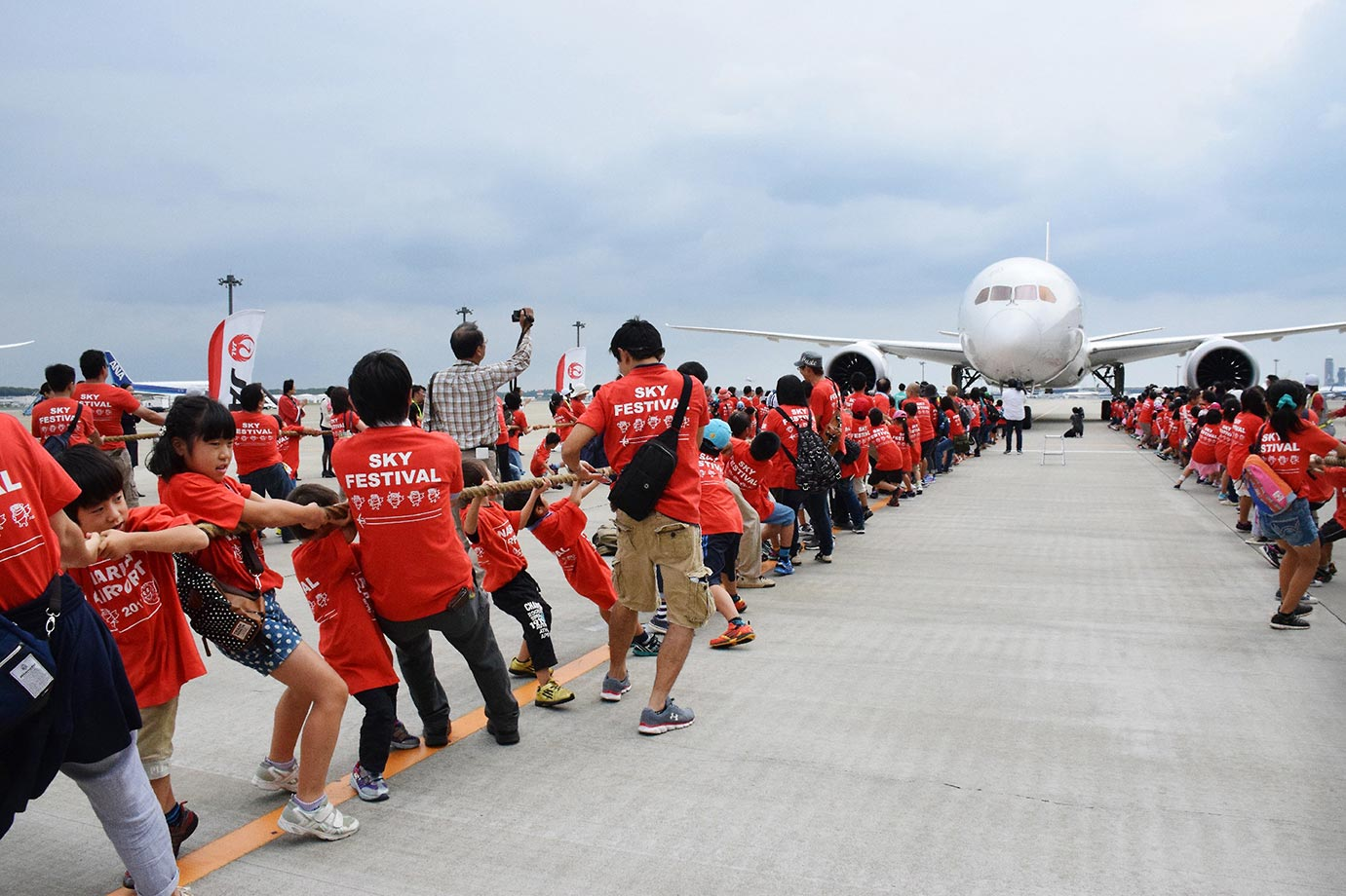 One-hundred-sixty-six elementary school children and their 112 parents pull a Boeing 787 jetliner at the Narita International airport in Narita, suburb of Tokyo.