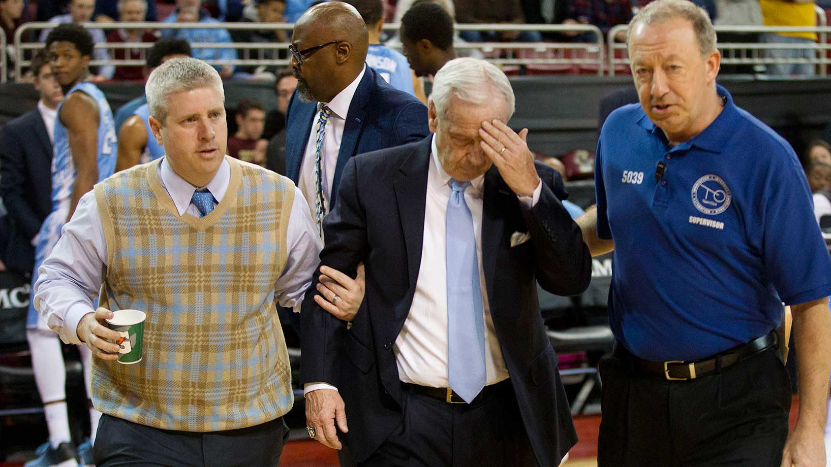 North Carolina's Roy Williams is escorted off the court after he appeared to faint and then sat on the floor surrounded by players.