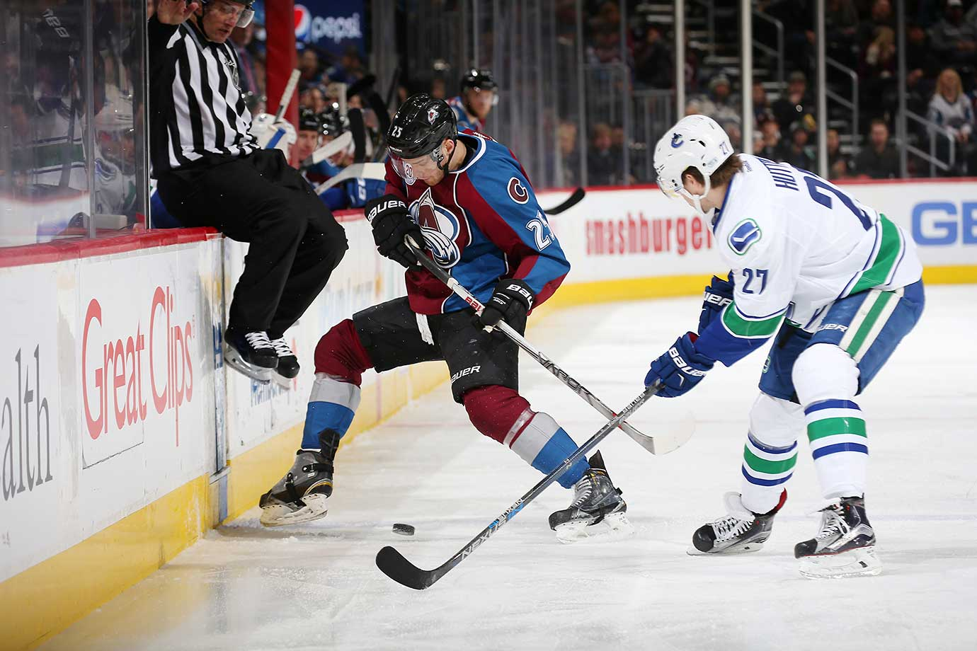 An official tries to get out of the way of Colorado's Mikhail Grigorenko and Vancouver's Ben Hutton.