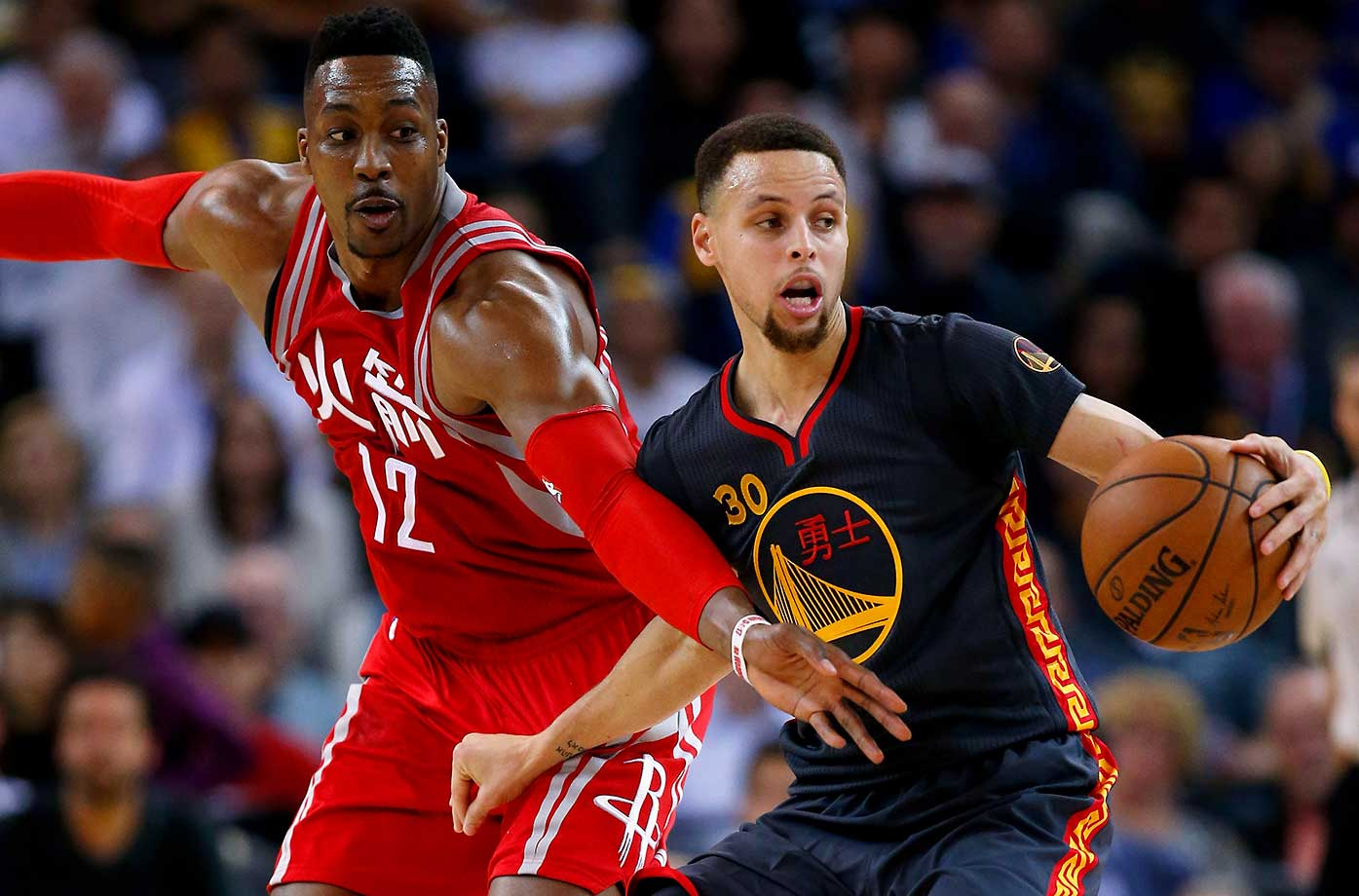 Dwight Howard of the Houston Rockets tries to steal the ball from Stephen Curry.