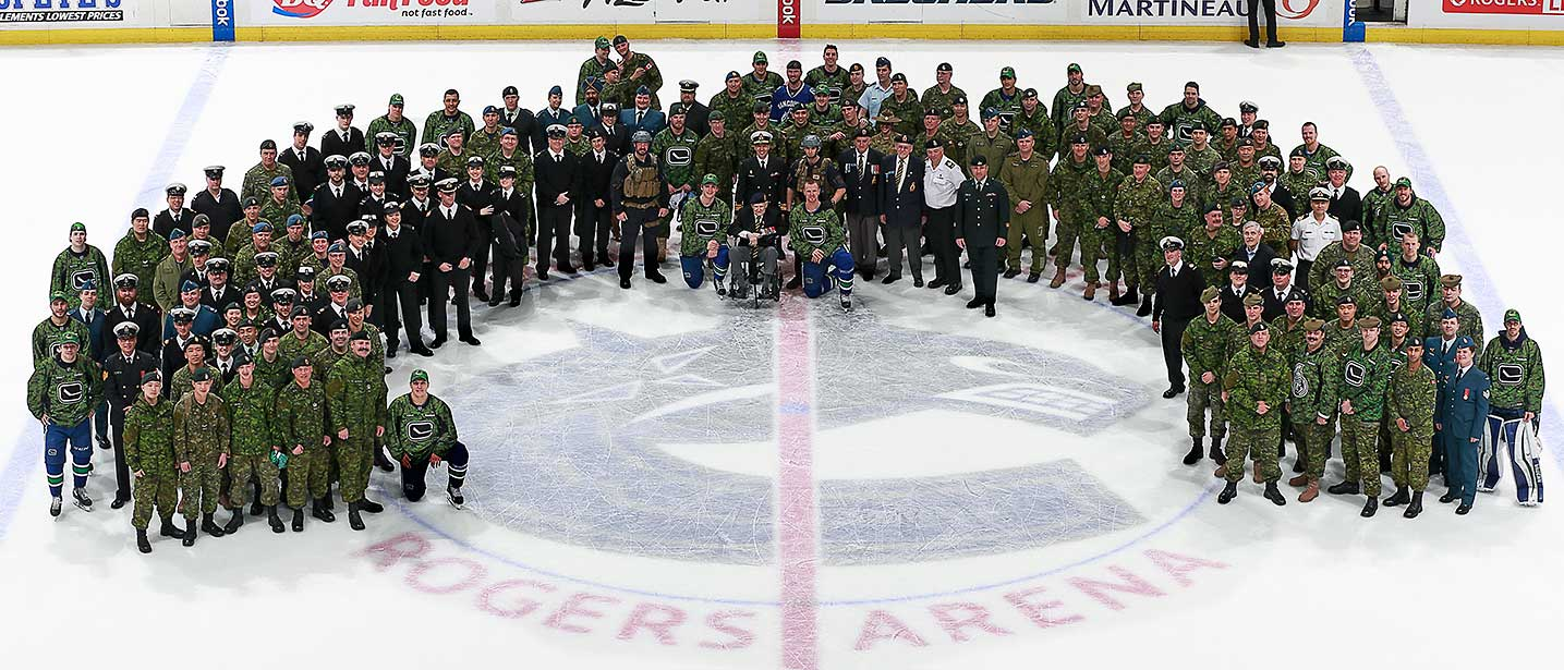 The Vancouver Canucks pose for a group photo with Canadian military personnel after their game against Ottawa.