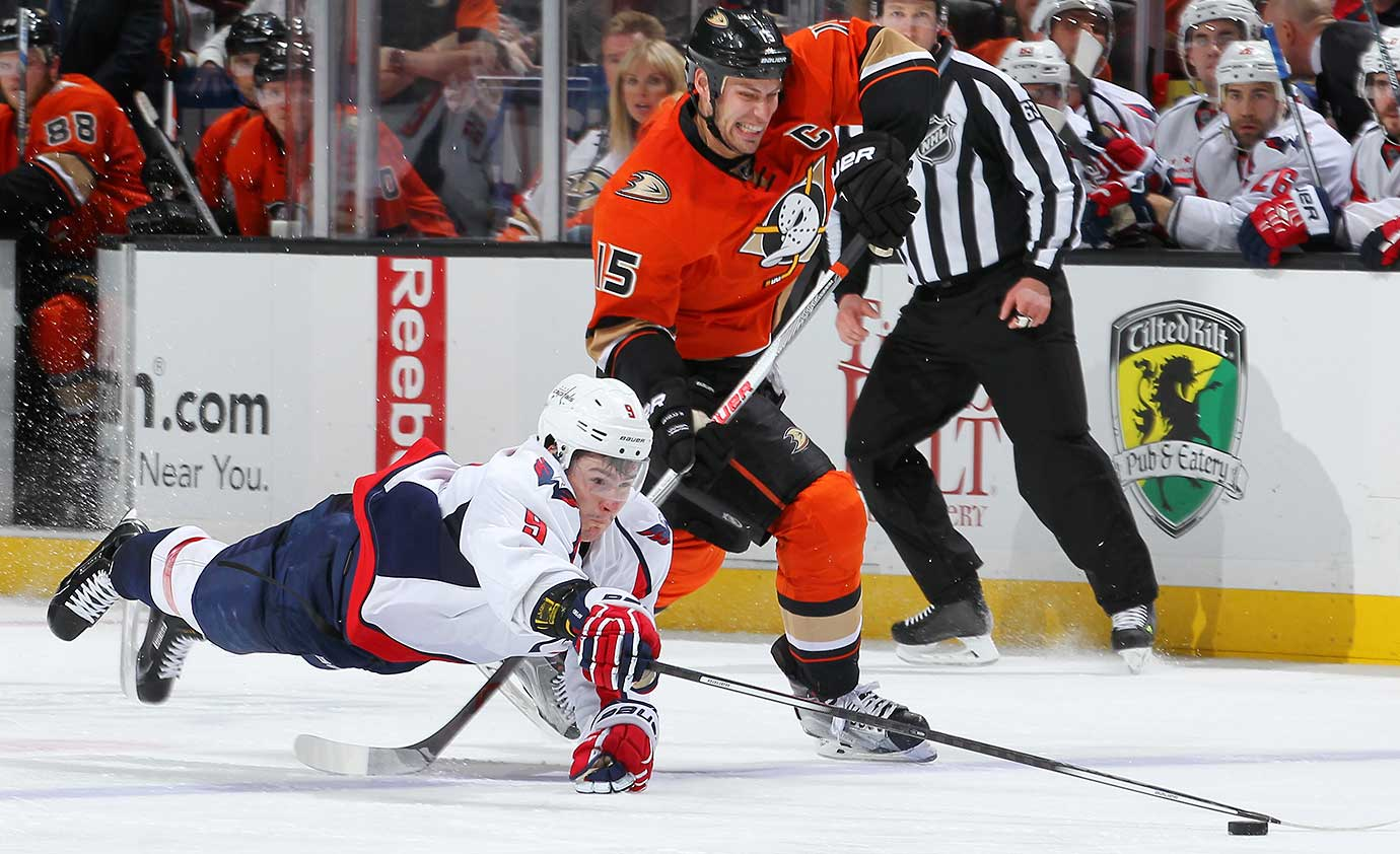 Dmitry Orlov of the Washington Capitals dives for the puck ahead of Ryan Getzlaf of the Anaheim Ducks.