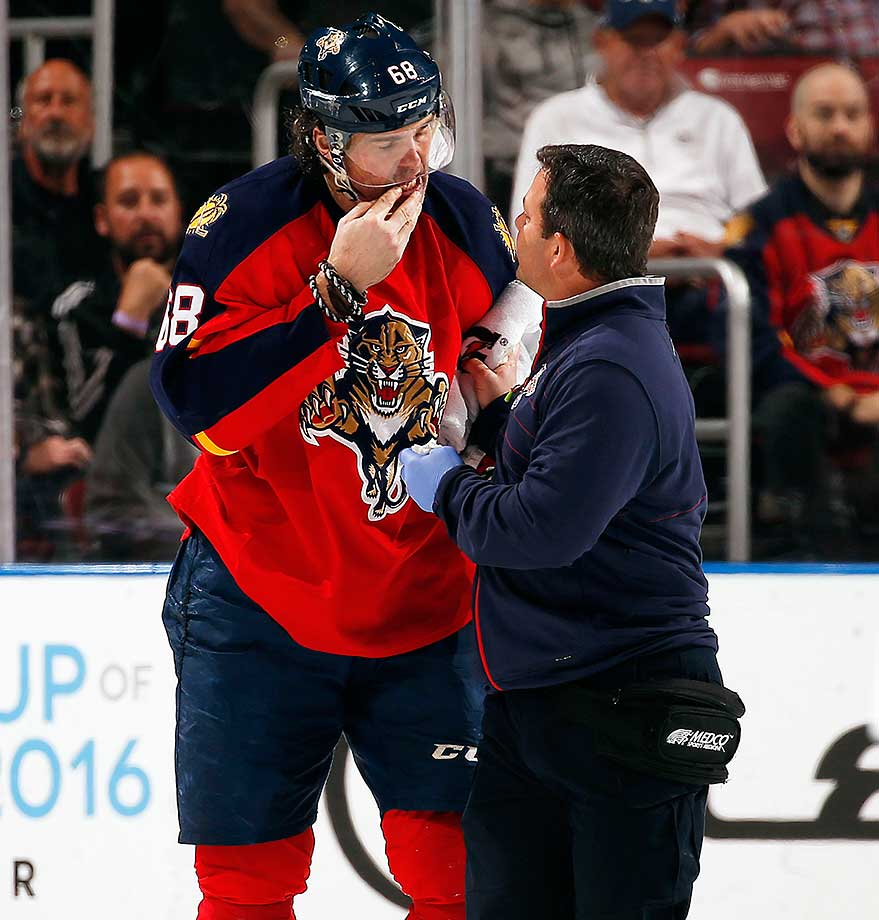 Jaromir Jagr of Florida is attended to by Dave Zenobi after being hit in the mouth with a stick again while playing Ottawa.