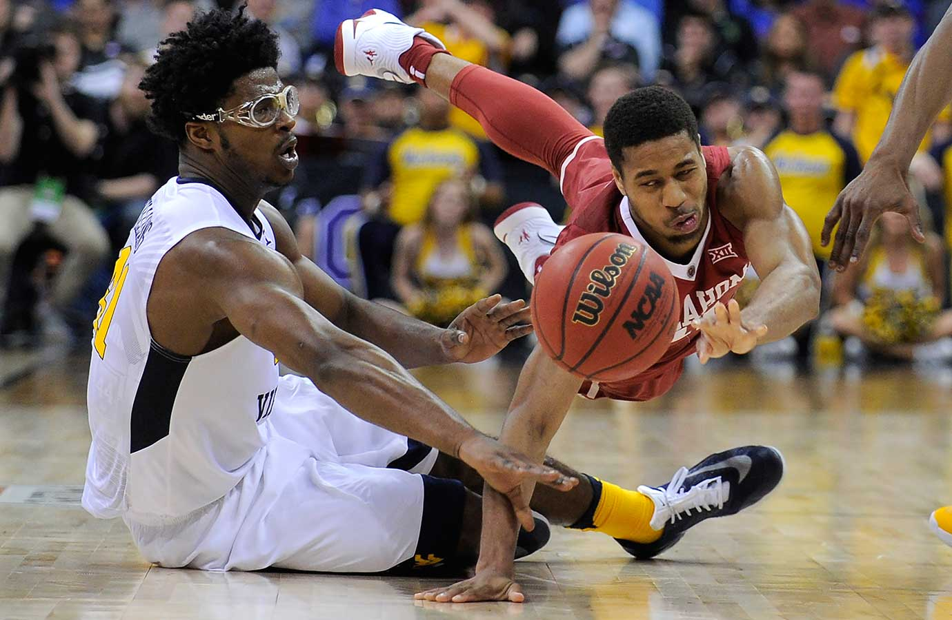 Isaiah Cousins of Oklahoma looses the ball and is charged with traveling against Devin Williams of West Virginia.