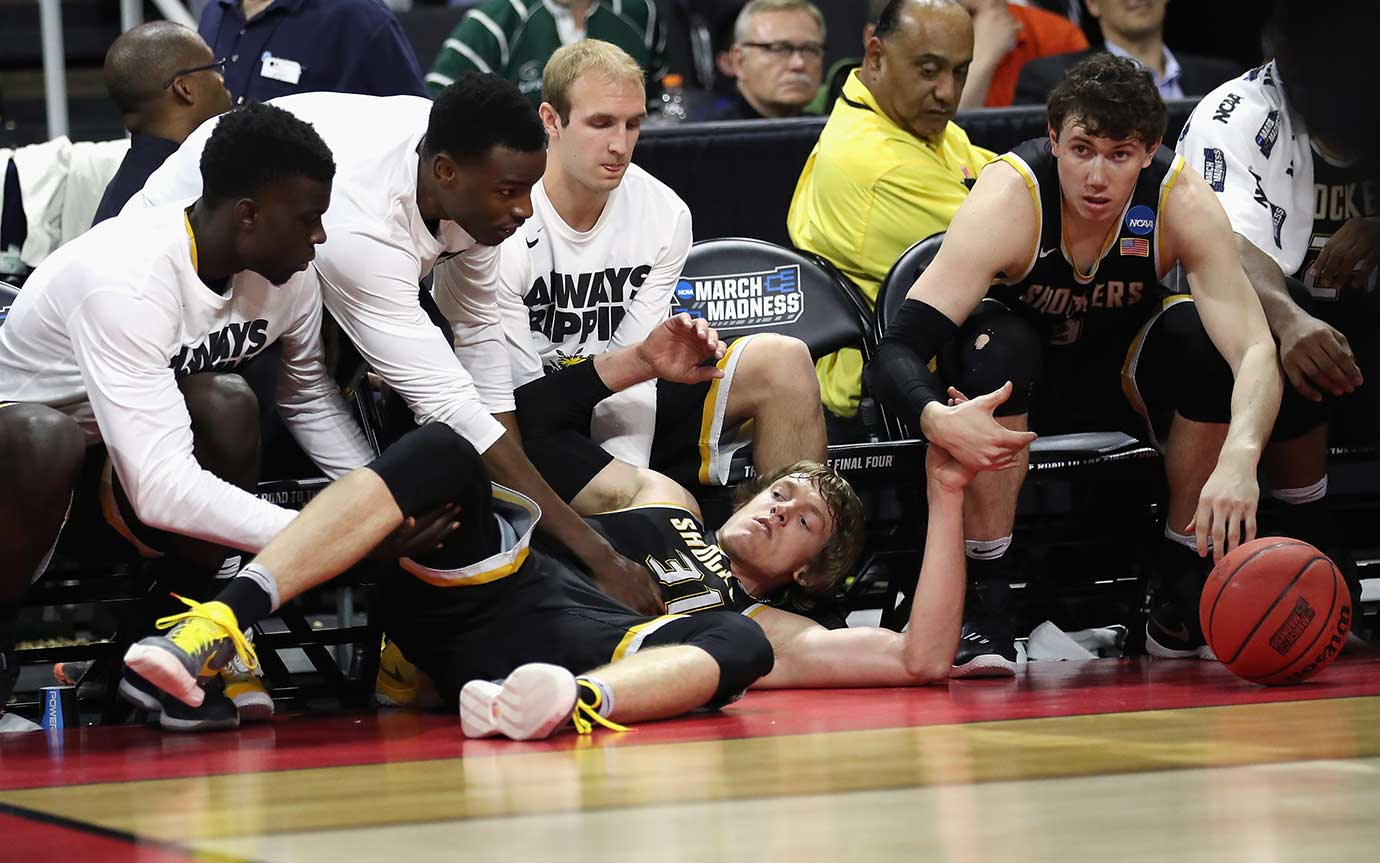 Ron Baker of Wichita State falls into the bench during a win over the Arizona Wildcats.