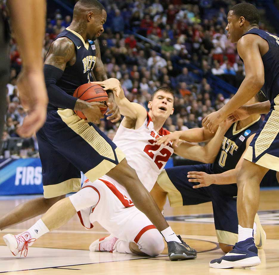 Wisconsin's Ethan Happ fouls Pittsburgh's Michael Young as they battle for possession. Wisconsin advanced, 47-43.