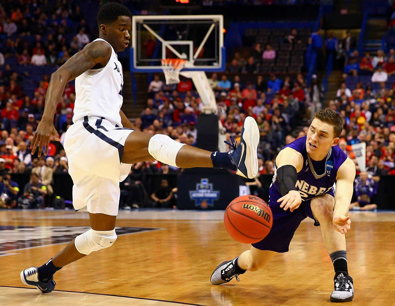 Edmond Sumner of the Xavier Musketeers attempts to block a pass by McKay Cannon of Weber State.