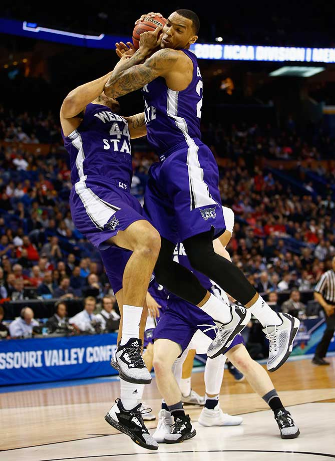 Zach Braxton and Joel Bolomboy of Weber State attempt to rebound the ballagainst the Xavier Musketeers.