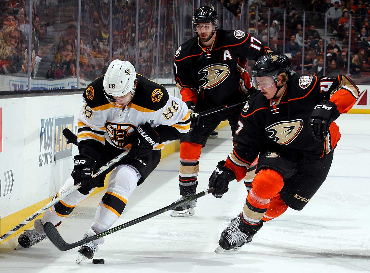 David Pastrnak of Boston skates over the puck with Hampus Lindholm of Anaheim defending.