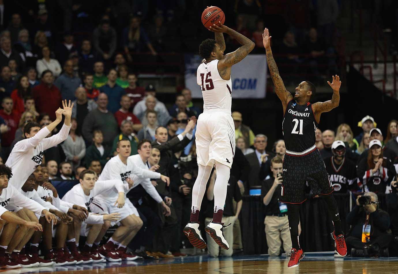 Isaiah Miles of the Saint Joseph's Hawks scores the game-winning basket against Farad Cobb of Cincinnati .