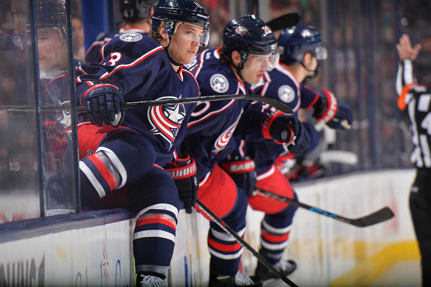 Cam Atkinson, Brandon Saad and Ryan Murray of Columbus climb over the boards during a game against New Jersey.