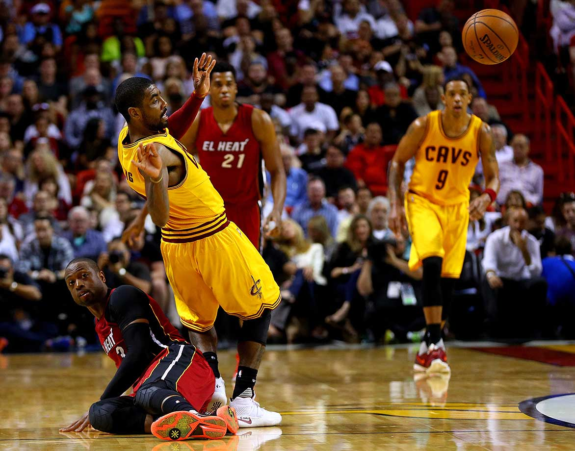 Dwyane Wade of the Miami Heat and Kyrie Irving of the Cleveland Cavaliers fight for a loose ball.
