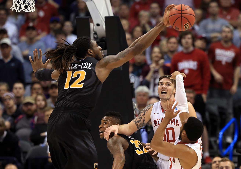 Mo Alie-Cox of VCU blocks a shot form Jordan Woodard of the Oklahoma Sooners.