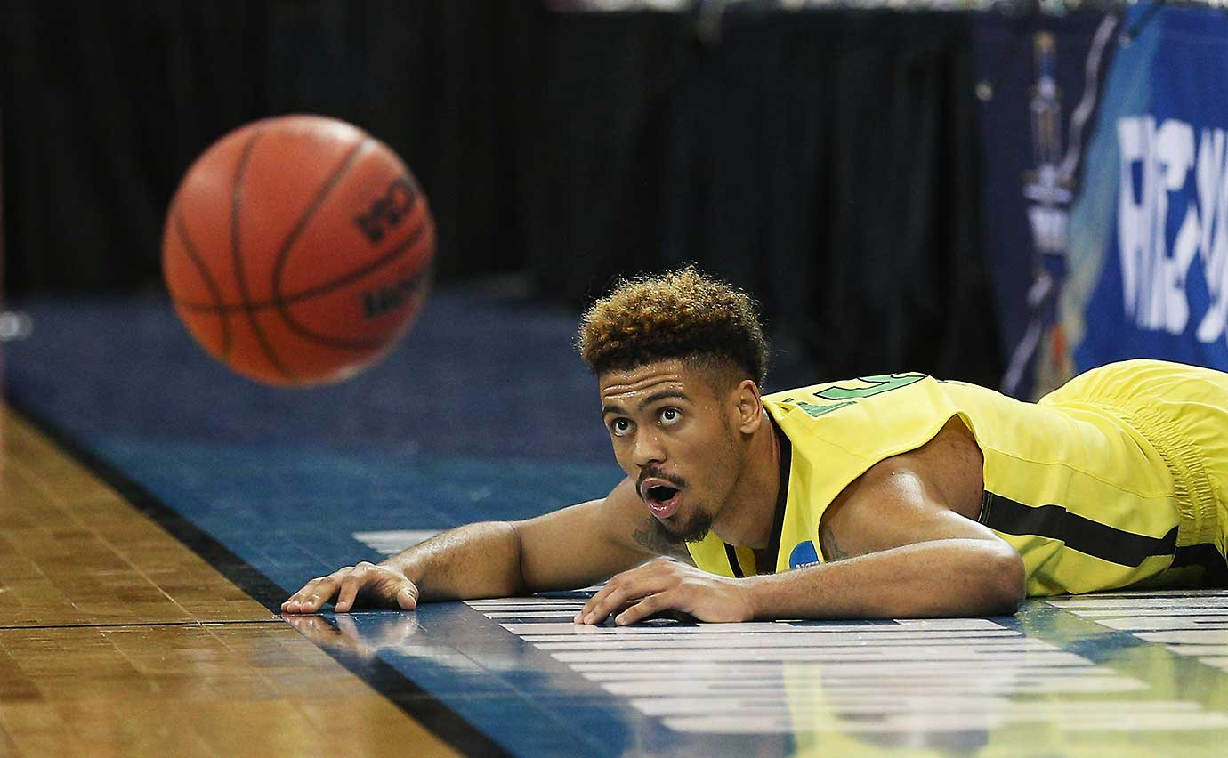 Tyler Dorsey of the Oregon Ducks watches the ball from the ground after he fought to keep it in bounds.