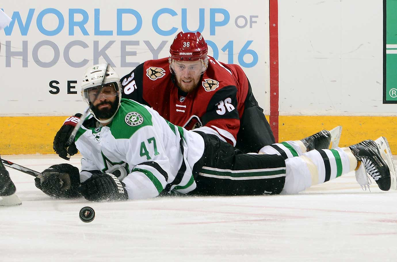 Johnny  Oduya of the Dallas Stars and Jiri Sekac of the Arizona Coyotes collide on the ice as the puck slides away.  (Photo by Norm Hall/NHLI via Getty Images)
