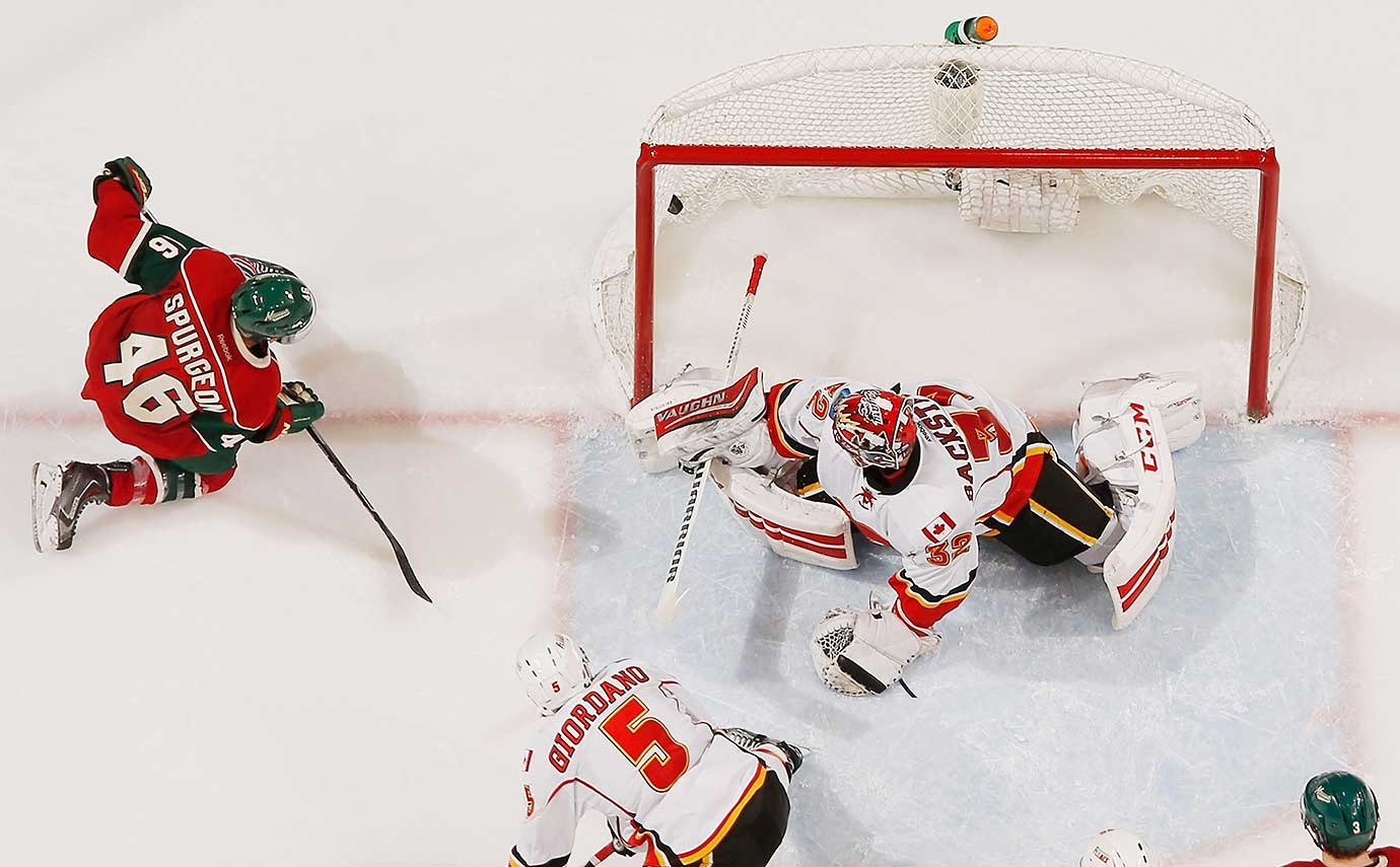 Jared Spurgeon of the Minnesota Wild scores a goal against Niklas Backstrom of the Calgary Flames.