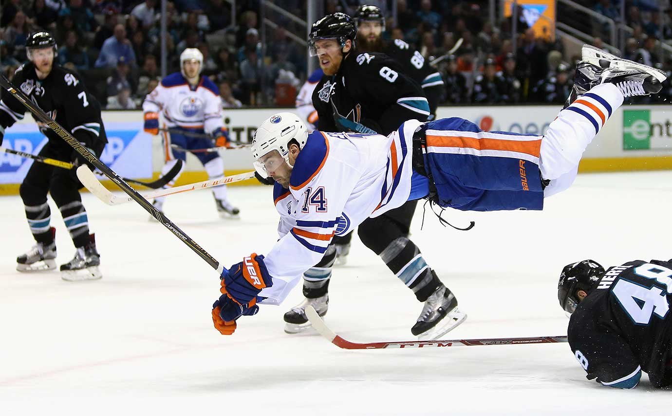 Jordan Eberle of the Edmonton Oilers goes airborne after hitting Tomas Hertl of the San Jose Sharks.