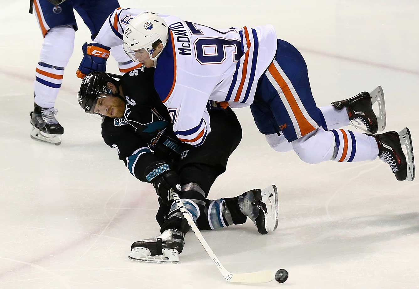 Connor McDavid of the Edmonton Oilers hits Joe Pavelski of the San Jose Sharks.