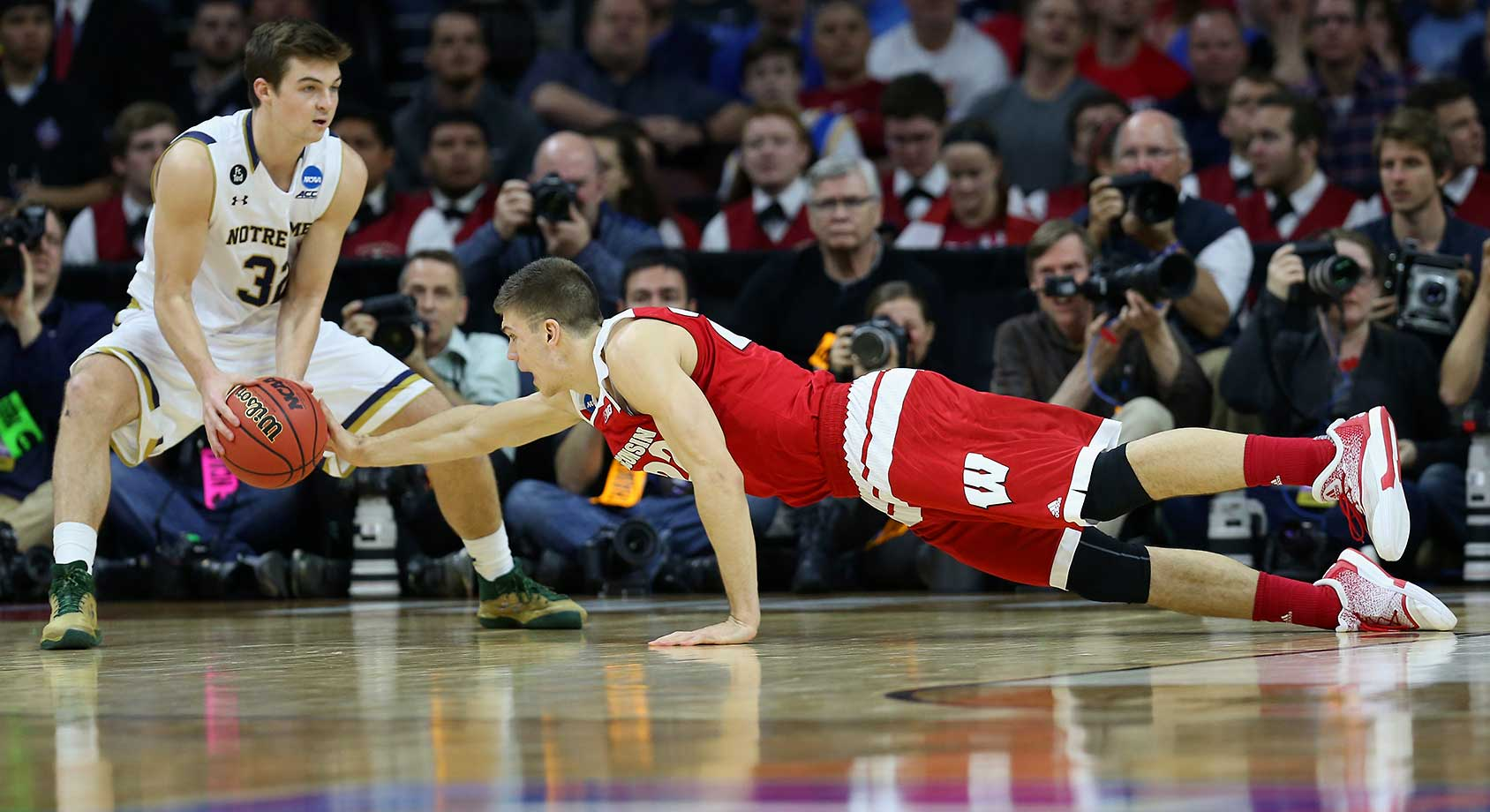 Ethan Happ of Wisconsin dives for the ball against Steve Vasturia of Notre Dame on a night in which the Badgers had 17 turnovers.