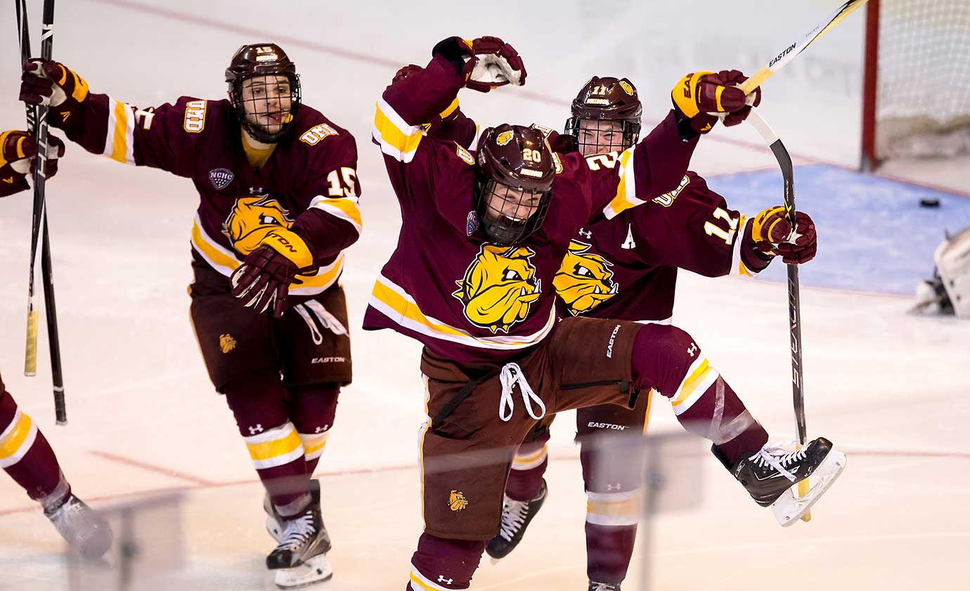 Karson Kuhlman of Minnesota Duluth celebrates his double overtime winning goal against Providence with teammates Willie Raskob (15) and Austin Farley during Game 1 of the NCAA Division I Northeast Regional Championship semifinals.