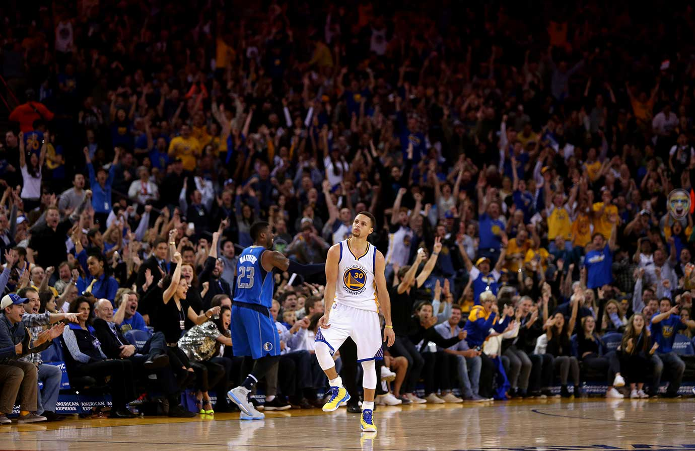 Stephen Curry reacts after making a shot near half court at the end of the first half against the Dallas Mavericks.