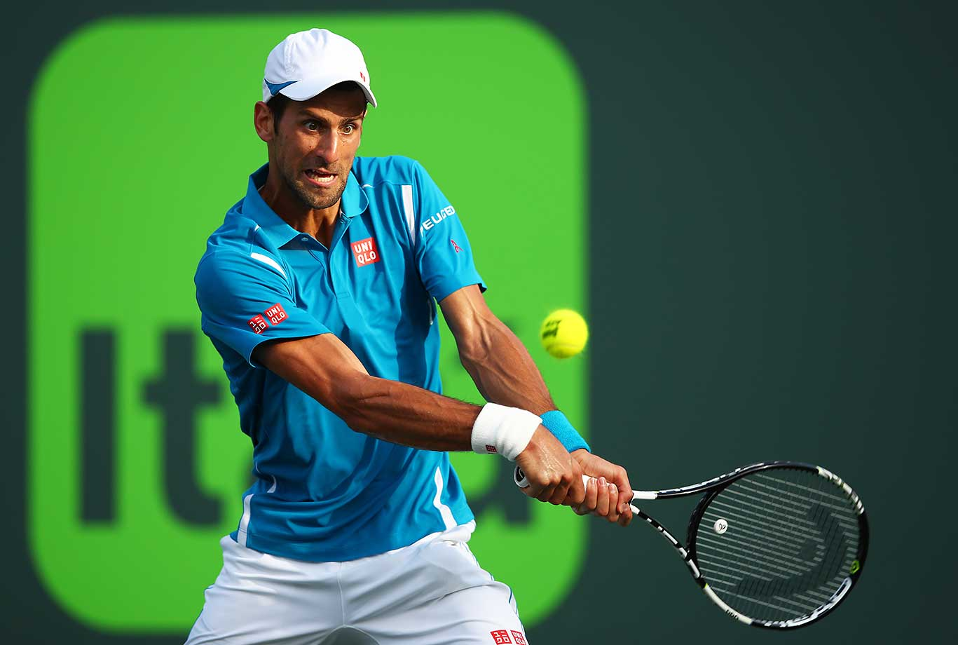 Novak Djokovic plays a backhand against Joao Sousa of Portugal in their third round match at the Miami Open.
