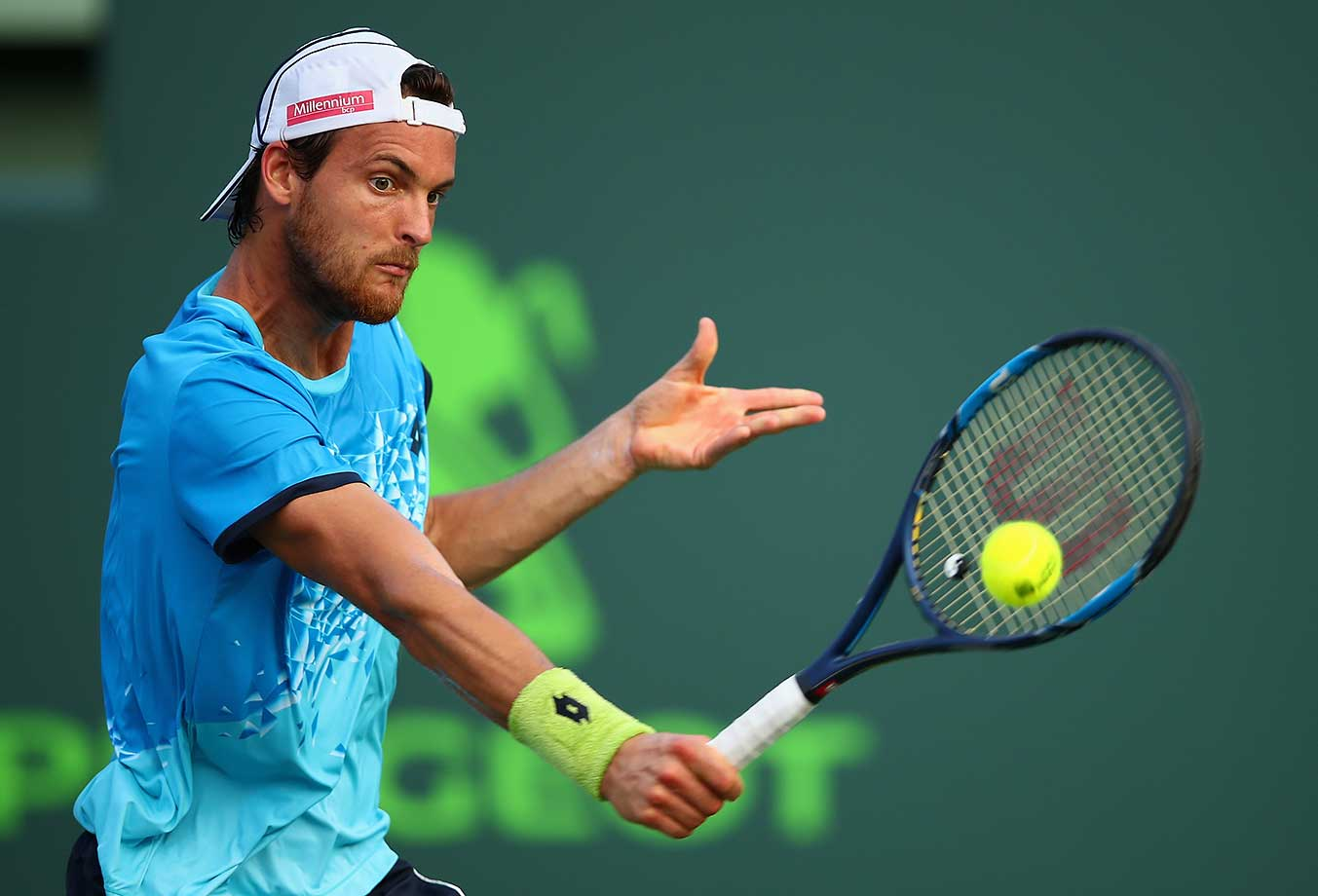 Joao Sousa of Portugal plays a backhand against Novak Djokovic in their third round match at the Miami Open.