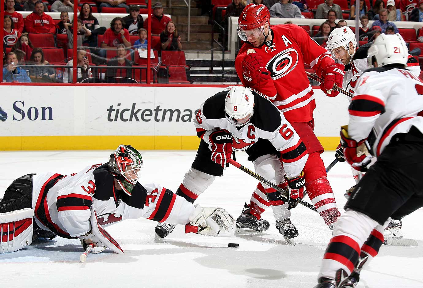 Scott Wedgewood of the New Jersey Devils dives outside the crease to make a glove save as teammate Andy Greene supports and Jordan Staal of the Carolina Hurricanes looks for an opportunity to deflect a loose puck.