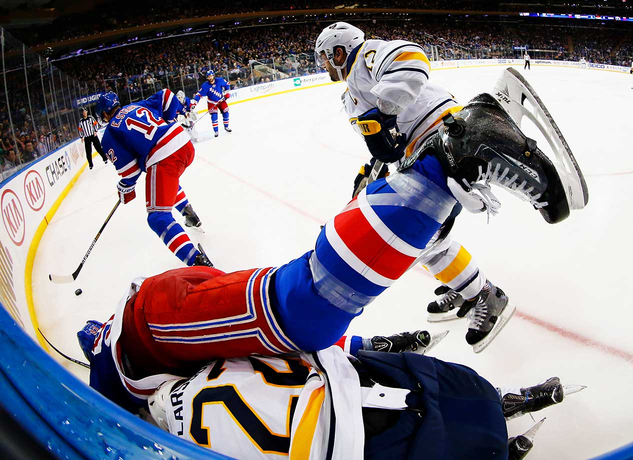 Keith Yandle of the New York Rangers falls over Johan Larsson of the Buffalo Sabres.