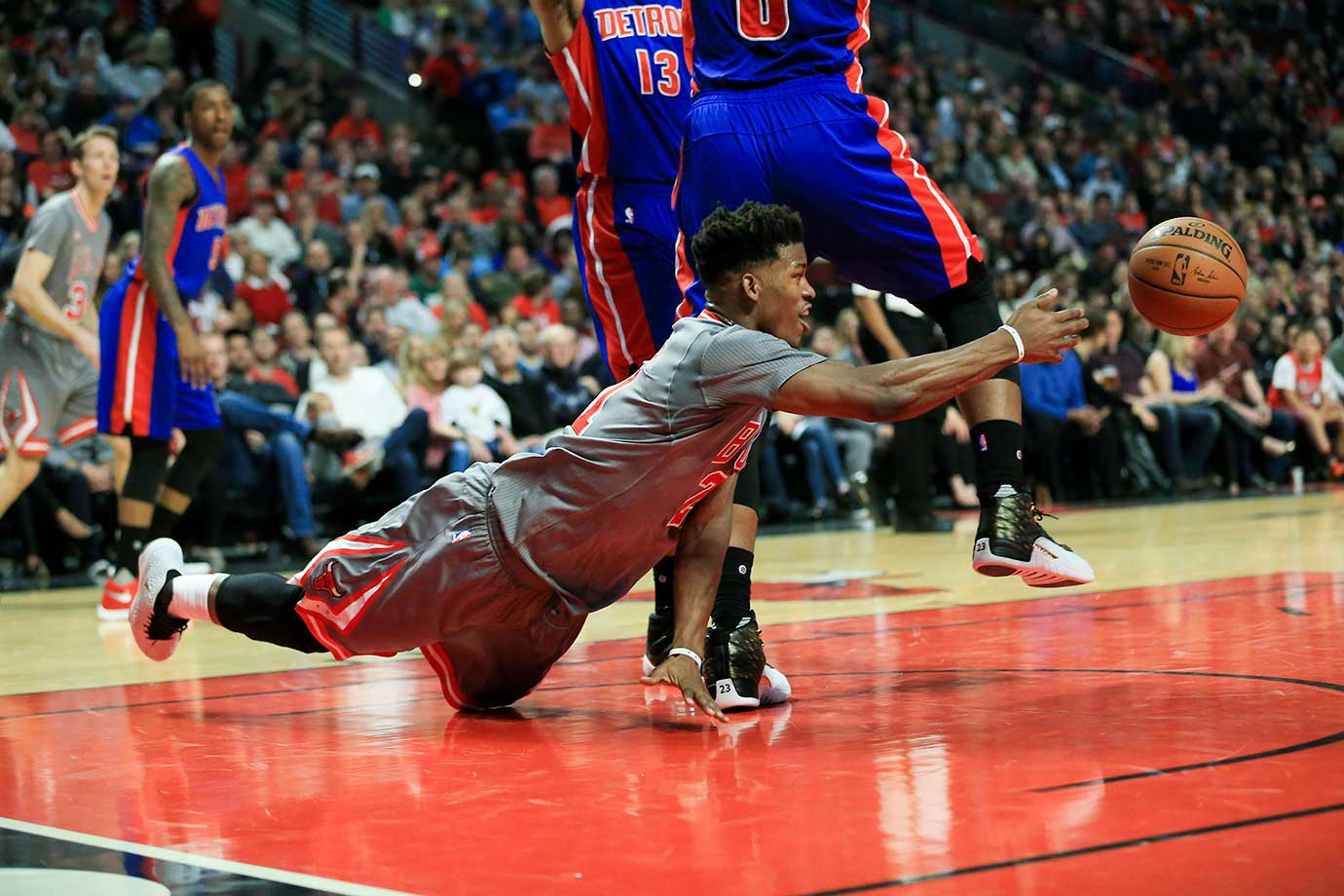 The Chicago Bulls' Jimmy Butler passes the ball around Andre Drummond of Detroit.