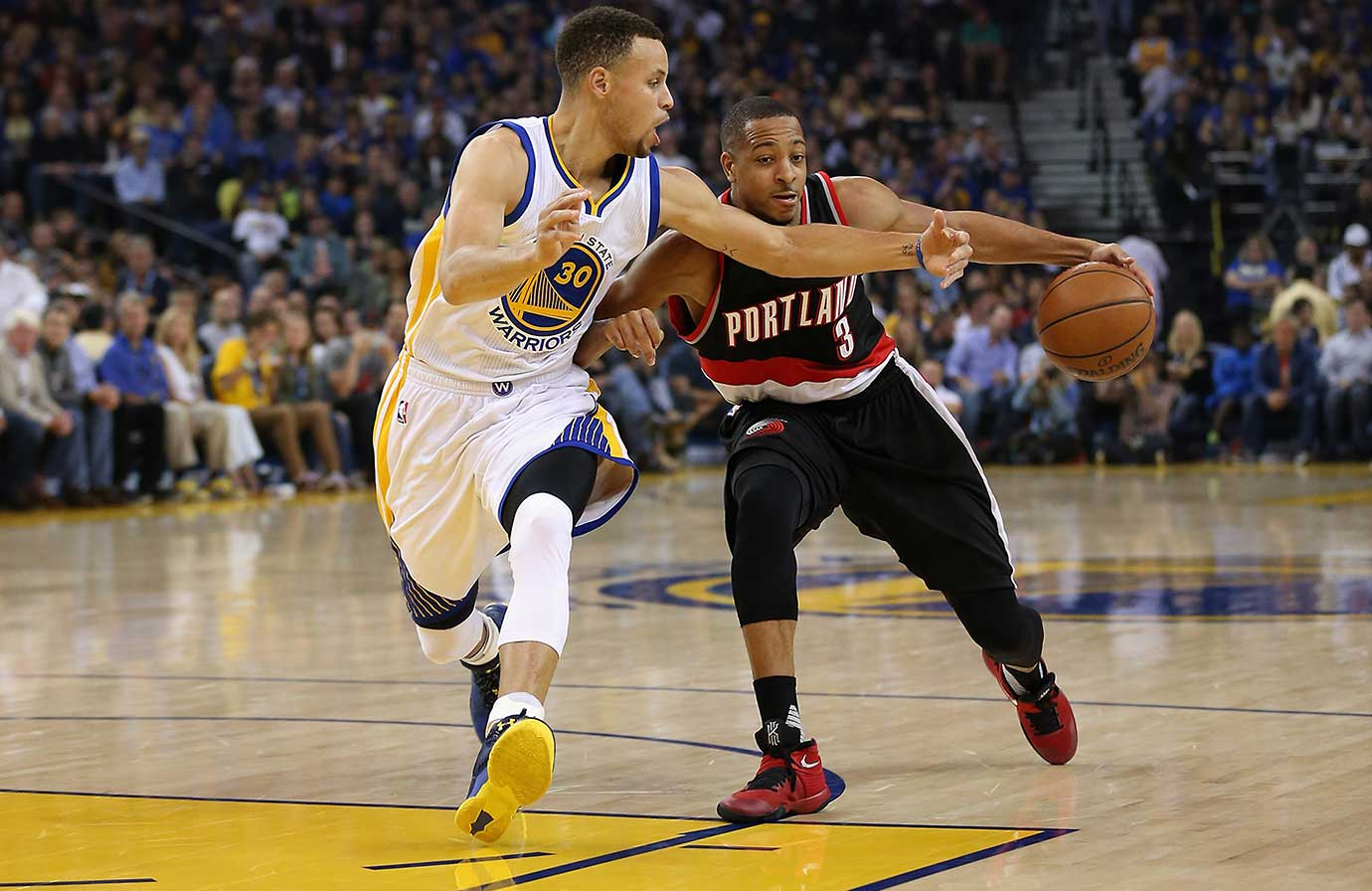 Stephen Curry of the Golden State Warriors tries to steal the ball from C.J. McCollum of the Portland Trail Blazers.
