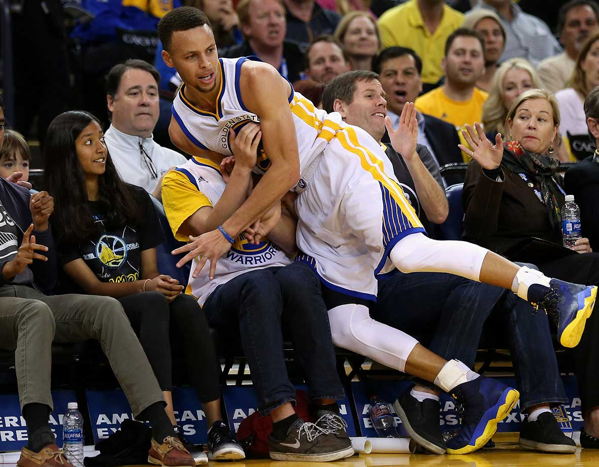 Stephen Curry lands on Golden State fans after chasing a loose ball during a game against the Portland Trail Blazers.