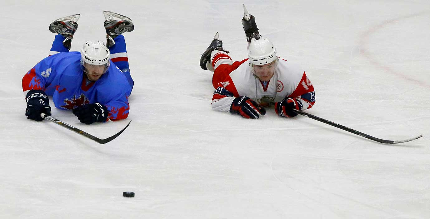 A Georgia and a Luxembourg player find themselves in a similar position during the IIHF Ice Hockey World Championships in Istanbul.