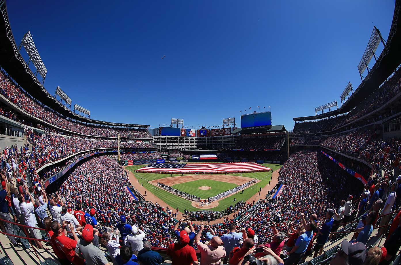 Fans look on as two fighter jets fly over during the National Anthem before the Texas Rangers take on the Seattle Mariners.