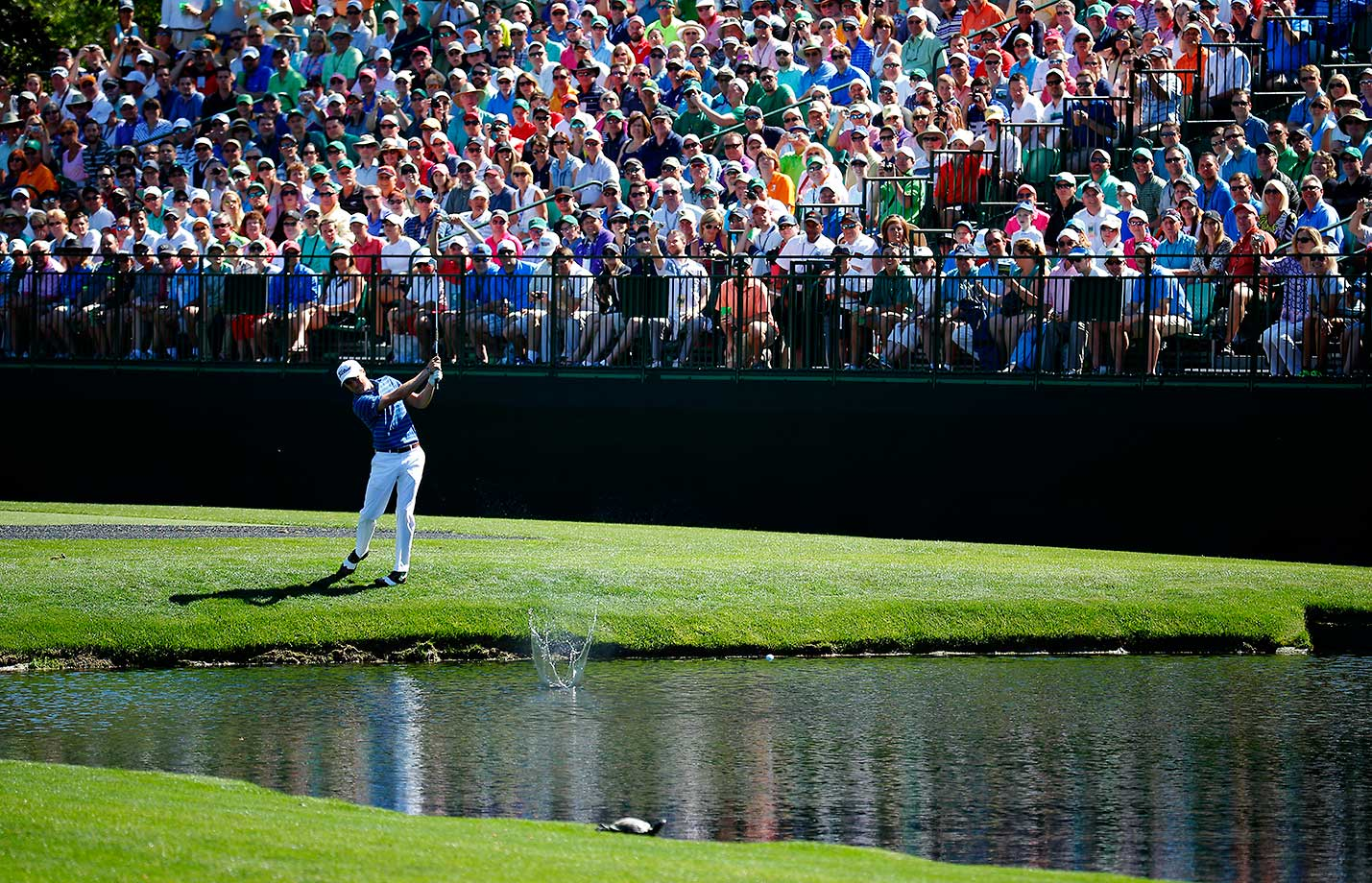 Justin Thomas skips a ball across the water on the 16th hole during a practice round prior to the start of the Masters.
