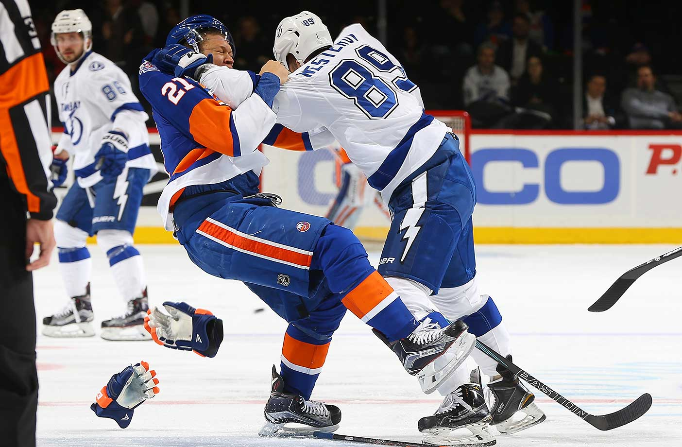 Kyle Okposo of the New York Islanders gets tangled up with Nikita Nesterov of the Tampa Bay Lightning.