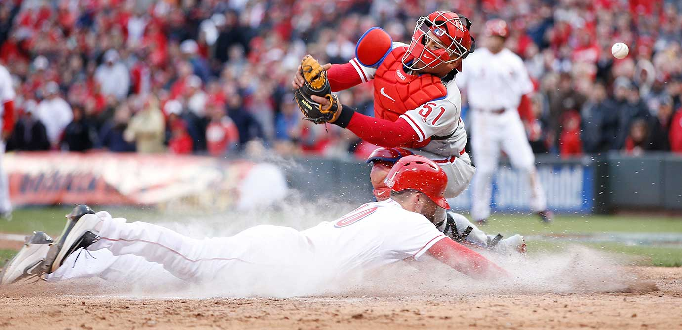 Tyler Holt of Cincinnati slides home with a run ahead of the throw to Carlos Ruiz of the Philadelphia Phillies.