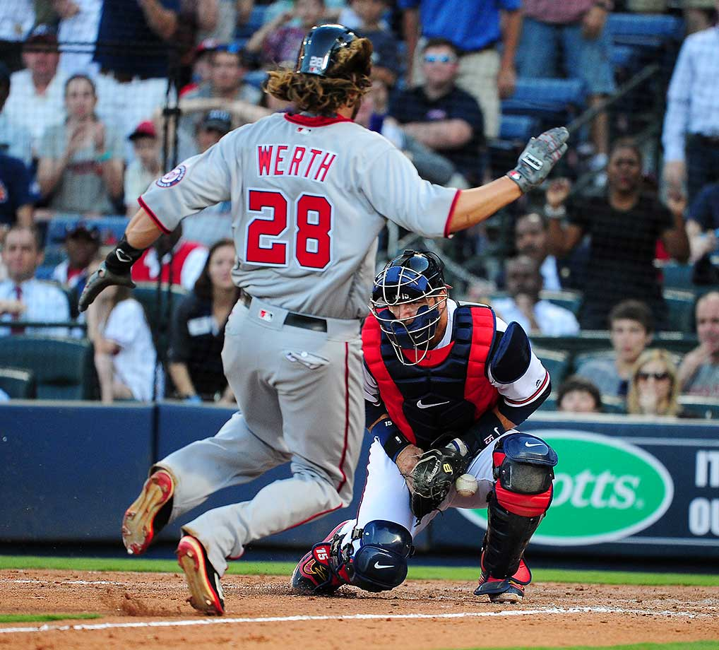 Jayson Werth of the Washington Nationals slides into home to score a ninth-inning run against A. J. Pierzynski of the Atlanta Braves.