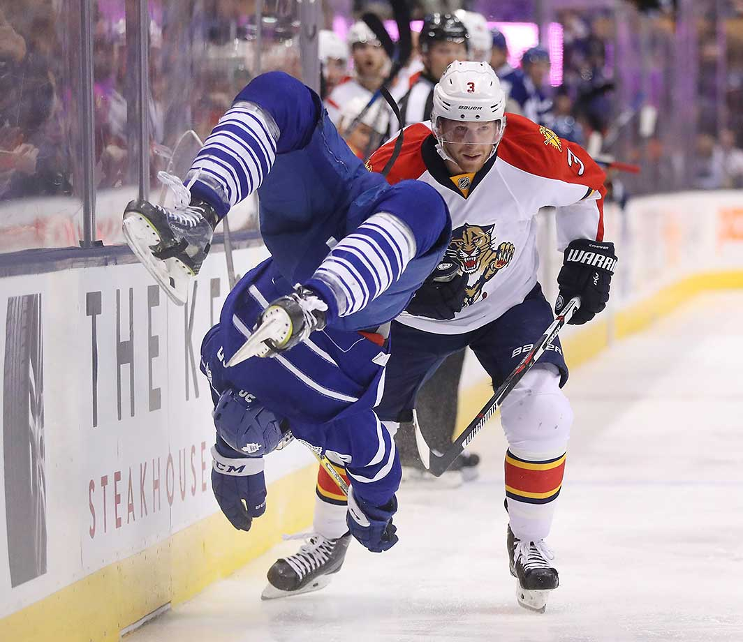 Florida Panthers defenseman Steven Kampfer sends Frank Corrado flying with a hip check.