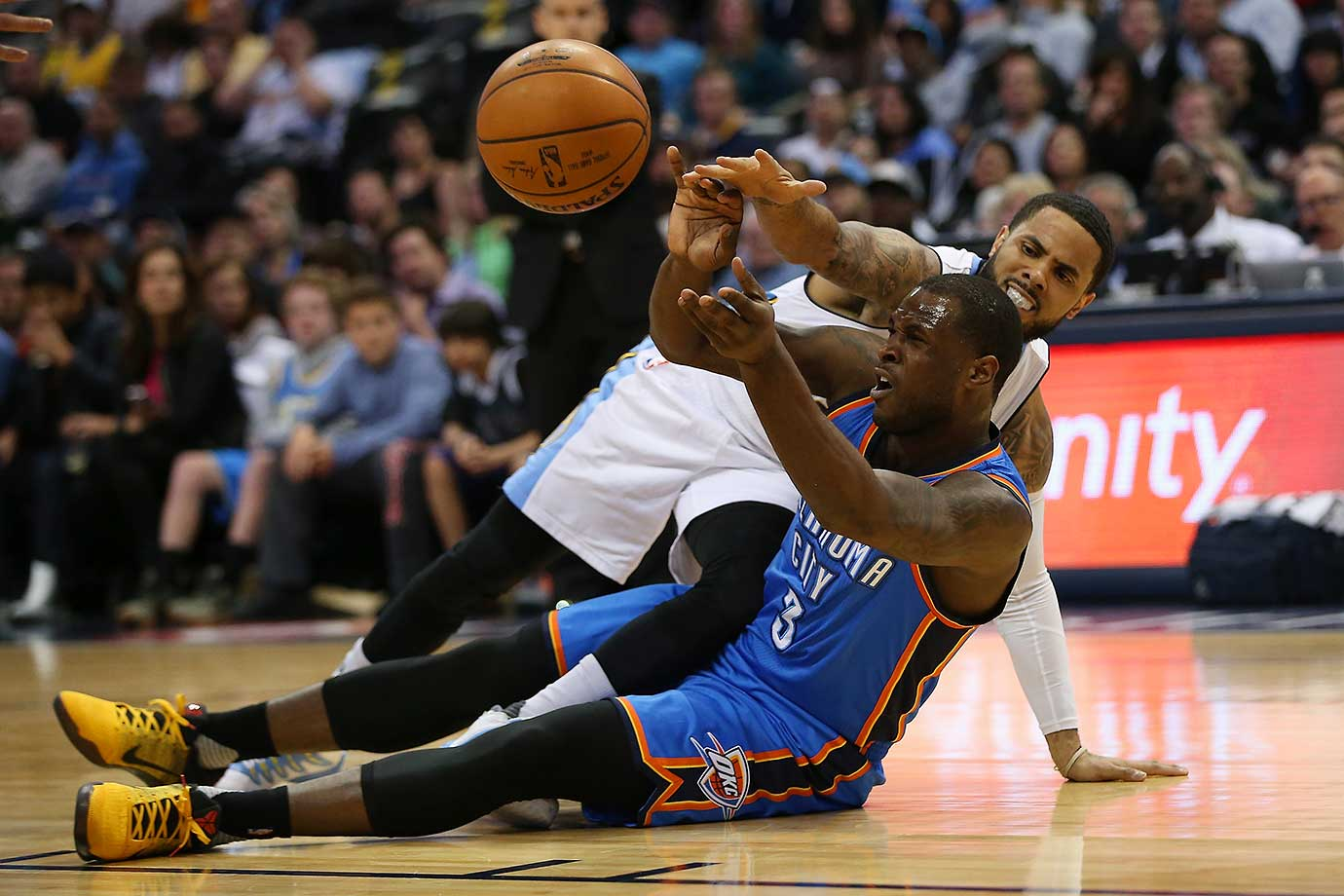 Dion Waiters of the Oklahoma City Thunder collects a loose ball against D.J. Augustin of the Denver Nuggets.