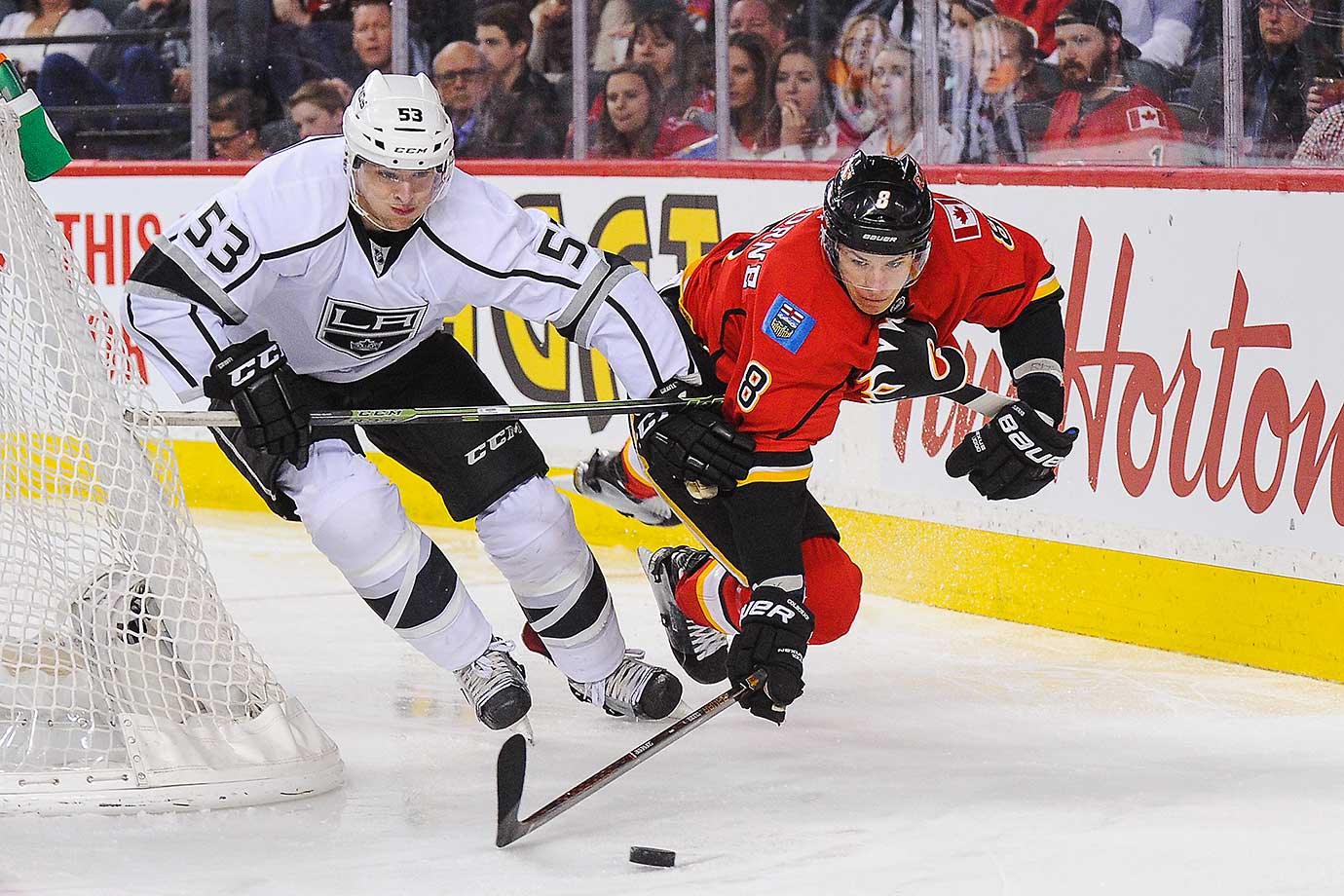 Joe Colborne of the Calgary Flames flies in the air while chasing the puck against Kevin Gravel of the Los Angeles Kings.