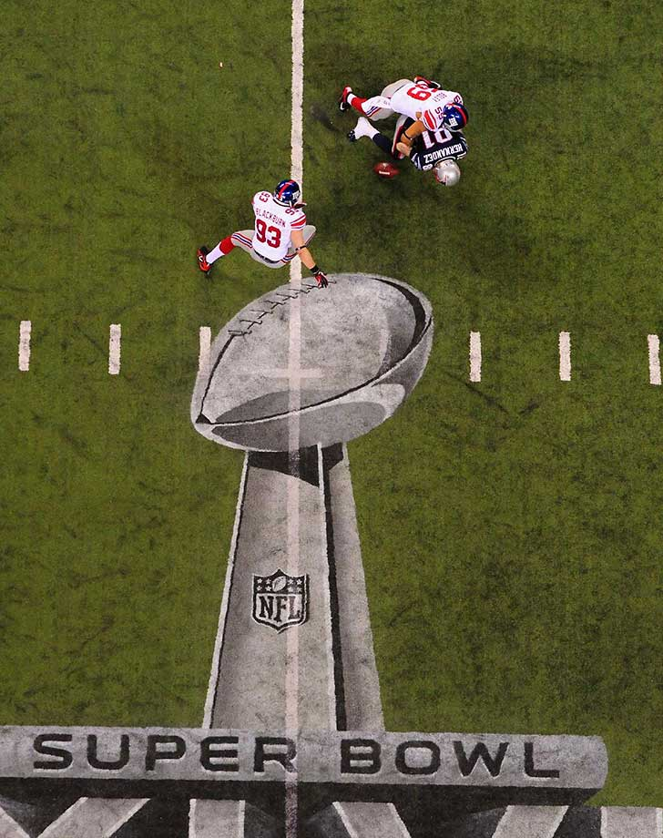 Aaron Hernandez looses the ball while being tackled by Michael Boley of the New York Giants in Super Bowl XLVI.