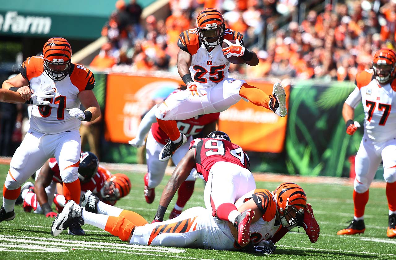 Giovani Bernard jumps over Jonathan Massaquoi of the Atlanta Falcons during the Bengals' 24-10 victory.